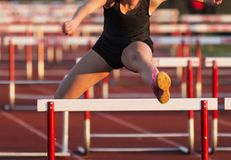 High school girls racing the 100 hurdles. A high school girl wearing a black uniform is raving in the 100 meter high hurdles at a local competition royalty free stock photo