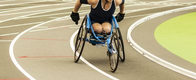 Wheelchair athlete racing on indoor track. A high school girl in a wheelchair is racing the mile on an indoor track stock photography