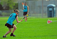 High school girls lacrosse. Player running down the field with possession of the ball as a defenders stick comes into frame royalty free stock image