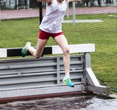 High school girls going over steeplechase barrier into water. A high school girls is racing the steeplechase during a competition Royalty Free Stock Photography