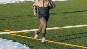 Running on field with snow in winter. High school girls running on a green turf field with a jacket on and snow surrounding her in the winter in New York Royalty Free Stock Photography