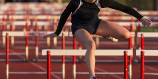 High school girls running a hurdles race. A high school girl is wearing a black uniform while running in a hurdles race at a track and field competition royalty free stock photography