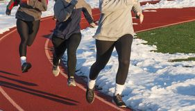Three girls running on a track at practice in the snow. High School girls running a workout on a track with snow shoveled off on to the e of it Royalty Free Stock Images