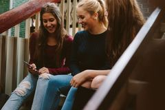 High school girls sitting on the stairs. Three young women sitting on the steps and looking at mobile phone. Group of high school girls sitting on the stairs Royalty Free Stock Image