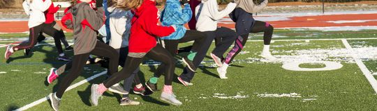 High school girls track team running on a snowy field. A high school girls track team is running on a turf field that still has snow on it during witnter track Stock Photos