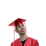 High School Graduate Future. Young high school graduate in red cap and gown looking up, thinking about his future plans, dreams, and aspirations stock photo
