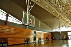 High school gym. Empty high school gym with basketball hoop and bleachers Stock Photo