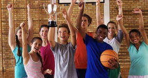 High school kids cheering while holding trophy in basketball court. Group of high school kids cheering while holding trophy in basketball court stock footage