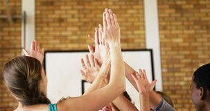 High school kids giving high five while holding trophy in basketball court. Group of high school kids giving high five while holding trophy in basketball court stock footage