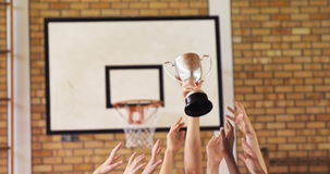 High school kids holding trophy in basketball court. Group of high school kids holding trophy in basketball court stock footage