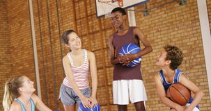 High school kids interacting with each other in basketball court stock video footage