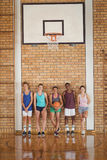 High school kids leaning against the wall in basketball court. Portrait of high school kids leaning against the wall in basketball court Stock Photo