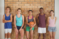 High school kids leaning against the wall in basketball court. Portrait of high school kids leaning against the wall in basketball court Royalty Free Stock Photography