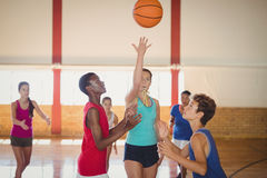 High school kids playing basketball in the court stock images