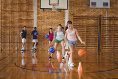 High school kids practicing football using cones for dribbling drill. In the court royalty free stock photography