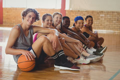 High school kids sitting on the floor in basketball court indoors stock photo