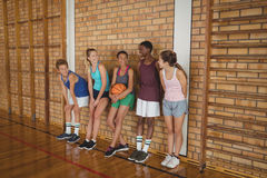 High school kids talking while leaning against the wall in basketball court. Smiling high school kids talking while leaning against the wall in basketball court stock photos