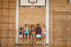 High school kids talking while leaning against the wall in basketball court. Smiling high school kids talking while leaning against the wall in basketball court Royalty Free Stock Images