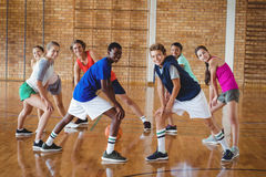 High school kids warming up in the court. Portrait of smiling high school kids warming up in the court Royalty Free Stock Images
