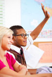 High School: Raising Hand to Answer Question. Extensive series of a multi-cultural group of students with a teacher, in a high school classroom setting Royalty Free Stock Photo