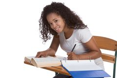 High school schoolgirl student by desk studying. Education series - ethnic black woman high school student sitting by school desk doing homework Royalty Free Stock Photo
