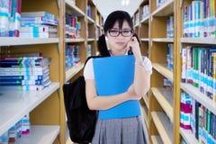 High School secundaria femenina que se coloca en la biblioteca Fotografía de archivo