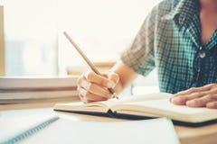 High School secundaria o estudiante universitario que estudia y que lee en biblioteca imágenes de archivo libres de regalías