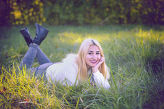 High School Senior Girl Laying in Grassy Field Stock Photo