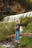 High School Senior Portrait Cute Male Outdoors. Senior Portrait of a handsome young man, outdoors full-length in front of a waterfall Royalty Free Stock Photos