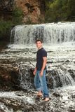 High School Senior Portrait Cute Male Outdoors. Senior Portrait of a handsome young man, outdoors full-length in front of a waterfall Royalty Free Stock Photo
