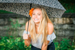 High school senior poses with umbrella for portraits on a rainy royalty free stock photos