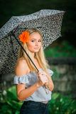 High school senior poses with umbrella for portraits on a rainy Stock Images