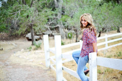High School Senior Sitting on Fence. High school senior girl outdoors sitting on fence Stock Images