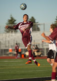 High School Soccer Player header. High School Soccer Player in the air heading the ball forward toward the goal Royalty Free Stock Photography