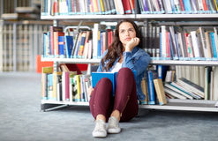 High school student girl reading book at library. Education, high school, university, learning and people concept - student girl reading book sitting on floor at Royalty Free Stock Photography