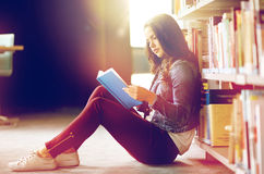 High school student girl reading book at library. Education, high school, university, learning and people concept - student girl reading book sitting on floor at Royalty Free Stock Images