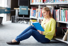 High school student girl reading book at library. Education, high school, university, learning and people concept - smiling student girl reading book sitting on Stock Photography