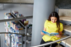 High school student girl reading book at library. Education, high school, university, learning and people concept - smiling student girl reading book sitting on Royalty Free Stock Photography