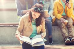 High school student girl reading book outdoors stock image