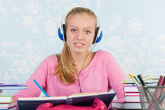 High school student with homework. High school student making homework at desk with music on headphones stock photography