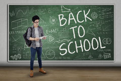 High school student standing in class. Full length of male high school student back to school and using digital tablet in class Royalty Free Stock Photography