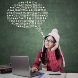 High school student thinking internet icons. Beautiful female high school student wearing winter clothes in the class and imagines internet icons Stock Image