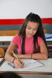 High School Student Writing In Book At Desk Stock Photo