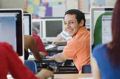 High School Students In Computer Laboratory. Portrait of a happy male student with classmates in computer laboratory Royalty Free Stock Photo