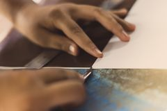 High school students are cutting prints and stickers using knife royalty free stock photos