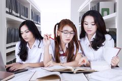 High school students doing schoolwork in library. Image of three high school students doing schoolwork together in the library Royalty Free Stock Photo