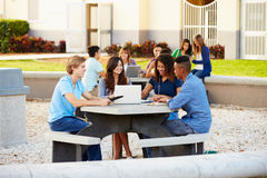 High School Students Hanging Out On Campus. Outside Sitting Around Table Stock Photos