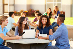 High School Students Hanging Out On Campus. Outside Using Laptop Stock Image