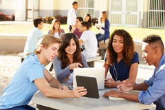 High School Students Hanging Out On Campus. Sitting Around Table Using Digital Tablet Stock Photo