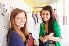 High School Students By Lockers Looking At Mobile Phone Stock Images